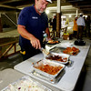 "KEN YUSZKUS/Staff photo  Windover/Beverly Crossing project superintendent Scott Martin digs into the barbeque lunch at the ""topping off"" ceremony for the new apartment complex, Windover/Beverly Crossing, at 131 Rantoul Street in Beverly.    09/06/16"