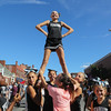 Photo/Reba Saldanha Peabody youth cheerleader Emma Jandrisevits is held up by her teammates in the middle of Washington St at the international festival in downtown Peabody Sunday Sept 11, 2016.