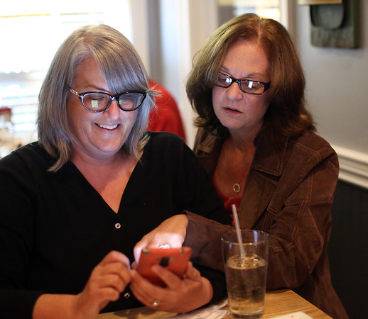 DAVID LE/Staff photo. Republican candidate for Essex County Sheriff Anne Manning-Martin, right,  and her sister Mary-Ellen Manning, anxiously check polling results at her election party held at Kelley Square Pub in Peabody on Thursday night. Manning-Martin got the Republican nomination after beating out the other candidates. 9/8/16.