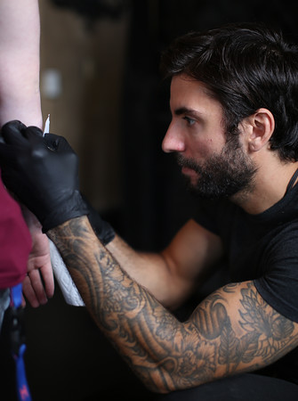DAVID LE/Staff photo. Matt Murray, and his identical twin brother Ryan, own and run Black Veil Tattoo Studio on Cabot Street in Beverly. The brothers were recently featured on Spike TV's Ink Master show. Matt carefully places a temporary stencil on a customer on Friday afternoon. 9/2/16.