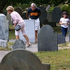 Tourists walk among the gravestones in The Burying Point cemetery