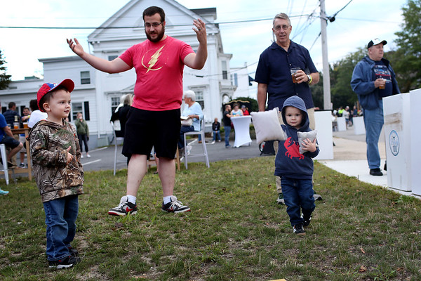 HADLEY GREEN/Staff photo<br /> From left, Caleb Gangi, Jim Gangi, Stephen Farrell, and Teddy Jackson, all of Peabody, play corn hole at Peabody's block party next to City Hall. <br /> 09/08/17