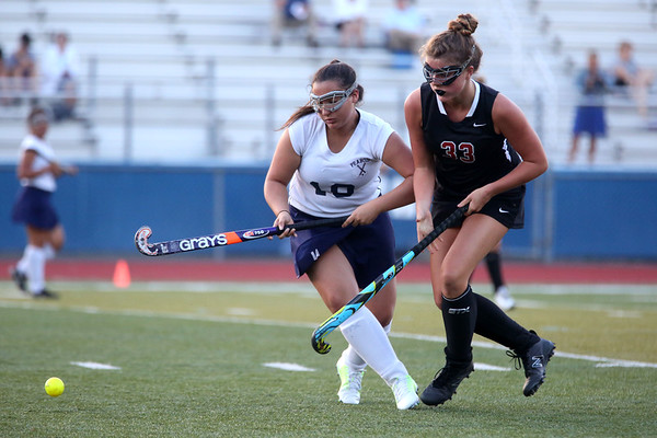 HADLEY GREEN/Staff photo<br /> Peabody's Gabriela Azevedo (19) and Marblehead's Amanda Schillinger (33) fight for the ball at the Peabody v. Marblehead girls varsity field hockey game at Peabody High School.<br /> 09/26/17