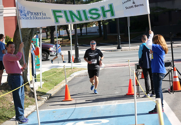 HADLEY GREEN/Staff photo<br /> Peabody police officer Sean Dowd crosses the finish line at the 16th annual International Race for Research to benefit the Progeria Research Foundation.<br /> 09/09/17
