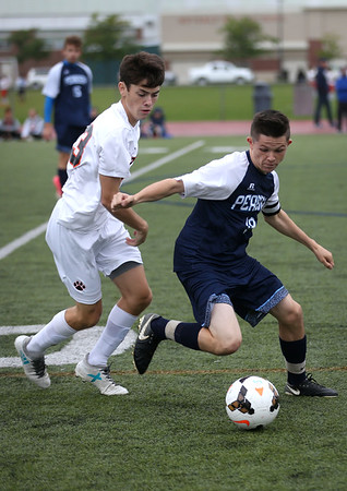HADLEY GREEN/Staff photo<br /> Peabody's Michael Panzini (18) dribbles the ball while Beverly's Ryan Kalampalikis (13) plays defense at the Beverly v. Peabody boys varsity soccer game at Beverly High School.<br /> 09/20/17