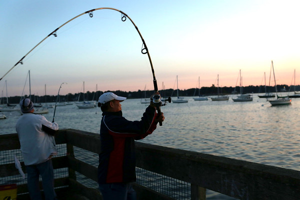 HADLEY GREEN/Staff photo<br /> Jose Valencia of Medford fishes for mackerel at sunrise off the pier at the Willows. Jose came on a quiet morning with his friend, Nick Sison, left, of Salem. <br /> 08/31/17