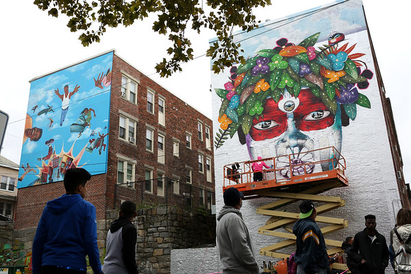HADLEY GREEN/Staff photo<br /> People watch while artist Chor Boogie paints his mural at the Punto Urban Art Museum opening party on Peabody Street in Salem.<br /> 09/30/17