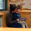 HADLEY GREEN/ Staff photo<br /> Camden Sterling, 3, smiles as his mom, Jodi, reads aloud a book in the children's room at the Hamilton-Wenham Public Library.<br /> <br /> 09/24/2018