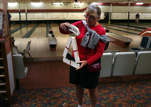 HADLEY GREEN/ Staff photo<br /> Judy Quinn of Beverly looks at a sign she claimed at Bowl-O-Mat's liquidation sale.<br /> <br /> 09/26/2018
