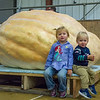 AMANDA SABGA/Staff photo <br /> <br /> Gracie, 3, and Charlie Hoyt, 1, of Amesbury sit in front of the giant pumpkin of a family friend during the Giant Pumpkin Weigh Off on the first night at Topsfield fair.<br /> <br /> 9/28/18