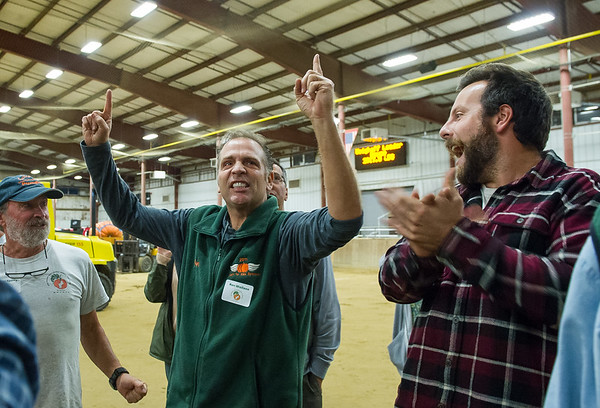 AMANDA SABGA/Staff photo <br /> <br /> Ron Wallace of Greene Rhode Island, center, celebrates as his 2114 pound pumpkin wins and breaks Topsfield Fair records during the Giant Pumpkin Weigh Off on the first night at Topsfield fair.<br /> <br /> 9/28/18