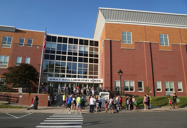 MIKE SPRINGER/Staff photo<br /> Students and parents gather outside the front door Wednesday morning for the first day of school at the new Horace Mann Laboratory School in Salem.<br /> 9/5/2018
