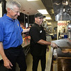 CARL RUSSO/staff photo. SALEM NEWS: Jim Boland, CEO/ owner of four local Fuddruckers watches his chef Hugo Rosario flip burgers at the Reading restaurant. Jim Boland, CEO/ owner of four local Fuddruckers shares his story about how he got involved in an annual cancer ride called A Reason to Ride. The ride was founded by a Peabody resident named Tom DesFosses. 9/6/2018