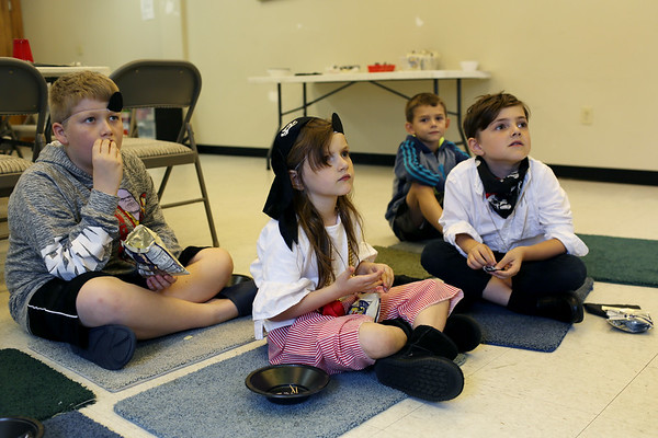 HADLEY GREEN/ Staff photo<br /> Children listen to librarian Betsy Reid read aloud pirate books at the Peabody Institute Library's Talk Like A Pirate Day event.<br /> <br /> 09/19/2018
