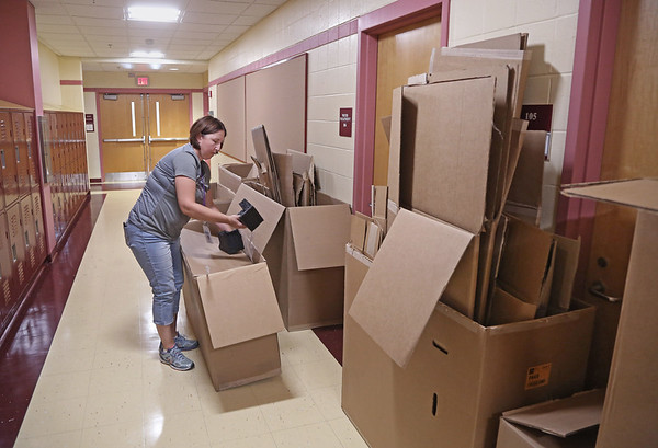 MIKE SPRINGER/Staff photo<br /> Social worker Lani Heath empties a box in the hallway as the Pathways for Children staff moved into its new space Friday at the Horace Mann Laboratory School in Salem.<br /> 9/7/2018