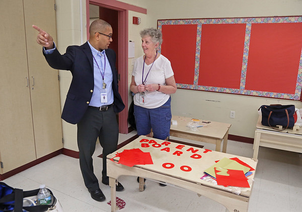 MIKE SPRINGER/Staff photo<br /> Eric Mitchell, vice president and chief operations officer of Pathways for Children, talks with teacher Bonnie Palmerini as the Pathways staff moved into its new space Friday at the Horace Mann Laboratory School in Salem.<br /> 9/7/2018