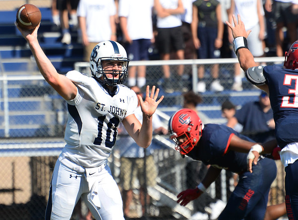CARL RUSSO/Staff photo. St. John's Quarterback, captain Matt Crowley passes the ball as Central defenders rush in.  St John's Prep defeated Central Catholic 28-14 in Saturday afternoon football action.  9/21/2019