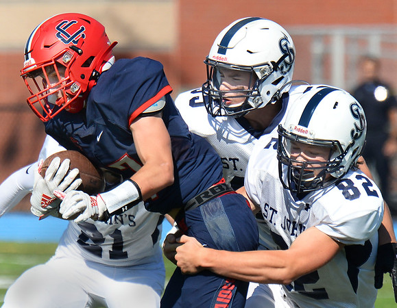 CARL RUSSO/Staff photo. Central's Dominic Tritto is surrounded and tackled by St. John's defenders, from left, Antonio Zarur, 21, Grady McGowan, top and Liam Fabbri, 82. St John's Prep defeated Central Catholic 28-14 in Saturday afternoon football action.  9/21/2019