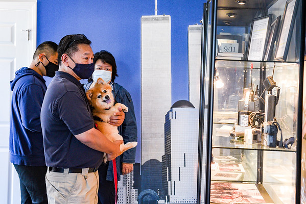 Communications Unit Leader Bill Yee holds his dog, Max, while being accompanied by his wife and son, Cindy and Nicky respectively, while viewing 9/11 artifacts during a ceremony in association with Historic Beverly at the Massachusetts Task Force 1 FEMA Urban Search & Rescue headquarters in Beverly. A ceremony takes place in observance of the 20th anniversary of the World Trade Center terror attacks in New York City on September 11, 2001.<br /> <br /> JAIME CAMPOS/Staff photo 9/11/2021