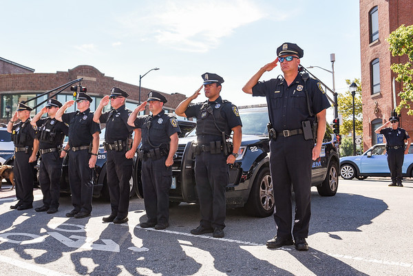 """Salem Police officers salute while the tune of """"Taps"""" is played during a ceremony at the Salem Fire Department in Salem in observance of the 20th anniversary of the World Trade Center terror attacks in New York City on September 11, 2001.<br /> <br /> JAIME CAMPOS/Staff photo 9/11/2021"""