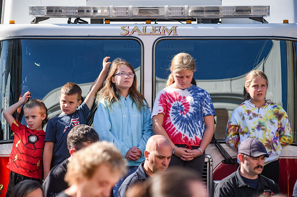 Children place stand on a firetruck's bumper while speeches are delivered during a ceremony at the Salem Fire Department in Salem in observance of the 20th anniversary of the World Trade Center terror attacks in New York City on September 11, 2001.<br /> <br /> JAIME CAMPOS/Staff photo 9/10/2021