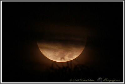 Very cloudy moon close to horizon