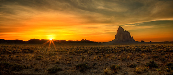 "Sunset, Shiprock, New Mexico. Shiprock, known in the Diné (Navajo) language as ""Tsé Bit'a'í"" (Rock With Wings) is the plug, or the solidified lava core, of a 40 million year old volcano. In the late 1800's white settlers believed the rock shape resembled a 19th century Clipper ship, and gave the peak it's english name.<br /> <br /> Although the peak has been climbed in decades past, it is now illegal to climb as it is a sacred place to the Diné. From what I've read, their legend states that long ago, the Gods created Tsé Bit'a'í as a sanctuary for the Diné to live upon and protect them from their enemies.<br /> <br /> After living on the peak for many years, a storm occurred while the men were tending crops in the fields below. Lightning struck and seared off the path that lead from the base to the top of the mountain, and being unable to escape, the women, children and old men stranded at the top starved to death over time. Because their remains were never removed according to this legend, it is considered sacrilegious to climb the mountain."
