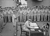 Toni on the USS Missouri with Fleet Admiral Nimitz and crew<br /> <br /> They are awaiting the Japanese envoys. In the meantime, Toni led the group in a rousing game of Categories, using P-E-A-C-E as the main word. The officer standing in the front row, fifth from the right, reportedly won the game.