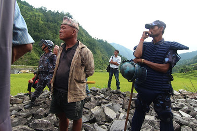 Local man, security forces, and a young engineer at the contested public hearing for the Trishuli 3B Hydropower Project. Pahirebesi, Nuwakot. 2013.