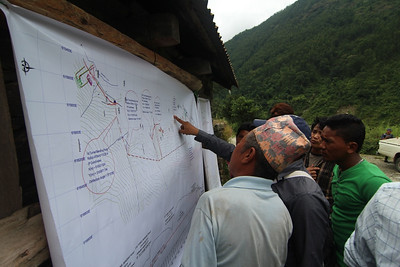 Local men perusing plans for the Trishuli 3B Hydropower Project at the September 2013 Public Hearing. The meeting was later obstructed by a local boycott of the EIA process. Pahirebesi, Nuwakot. 2013.