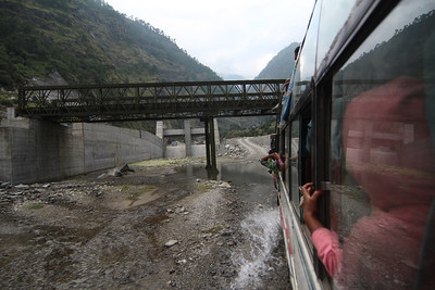 Bus travelling beneath the headworks consruction of the 90MW Trishuli 3A Hydropower Project (Chinese), upstream towards Mailung, site of the 216MW Upper Trishuli 1 Hydropower Project (Korean). Salleta, Rasuwa. 2013.
