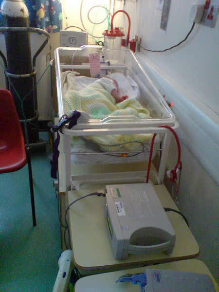 Amelia in her cot in Ealing Special Care.  Heart & Saturation monitor on the table in the foreground and the Apnea monitor in the cornew of the cot.<br /> As ever, she's rolled over and is facing the wall!