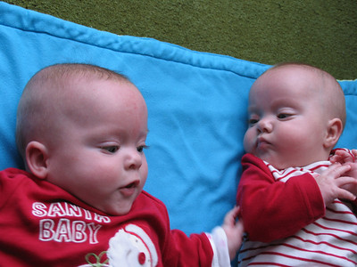"The girls on the mat at their Nanna & Grandad's at Christmas 2009, aged just 6 months and few days.  The ""Santa Baby"" outfits were a present from Dave & Andrea (thank you again) and became a firm favourite.  Bethany seems to be studying her sister, probably wondering why she's daring to touch her arm!"