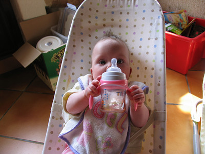 Baby hides from camera behind bottle. Daddy uses baby to hide beer box
