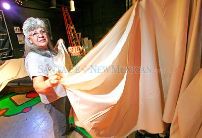 Theresa Valdez, from Santa Fe, helps a group from the Kiwanis Club hold up the 300 yards of muslin while it was getting sewn together to make Zozobra's dress on Aug. 24, 2010, at Warehouse 21.             Luis Sanchez Saturno/ The New Mexican.