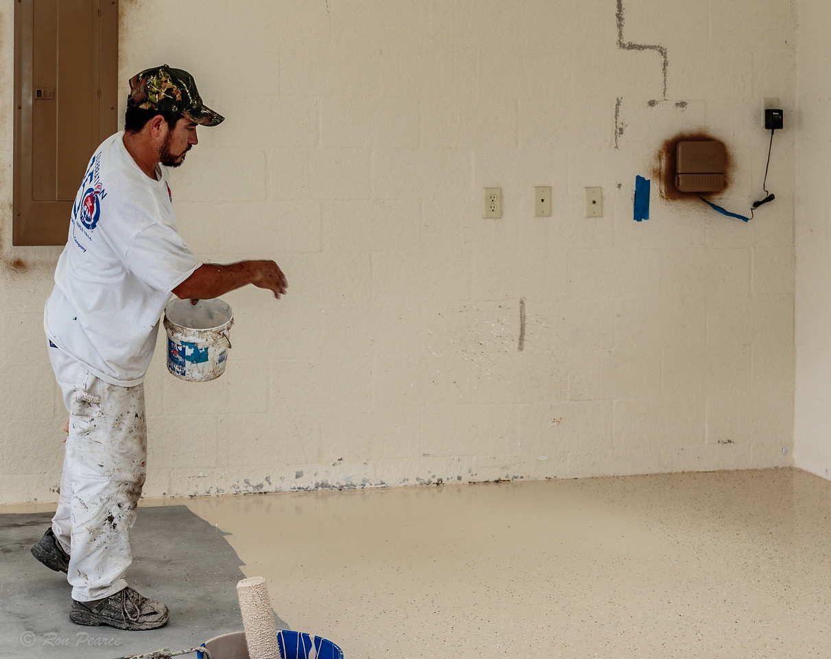 As the floor is being painted with the initial coat of paint, various colored specs of coloring are thrown randomly on the wet floor to add texture.