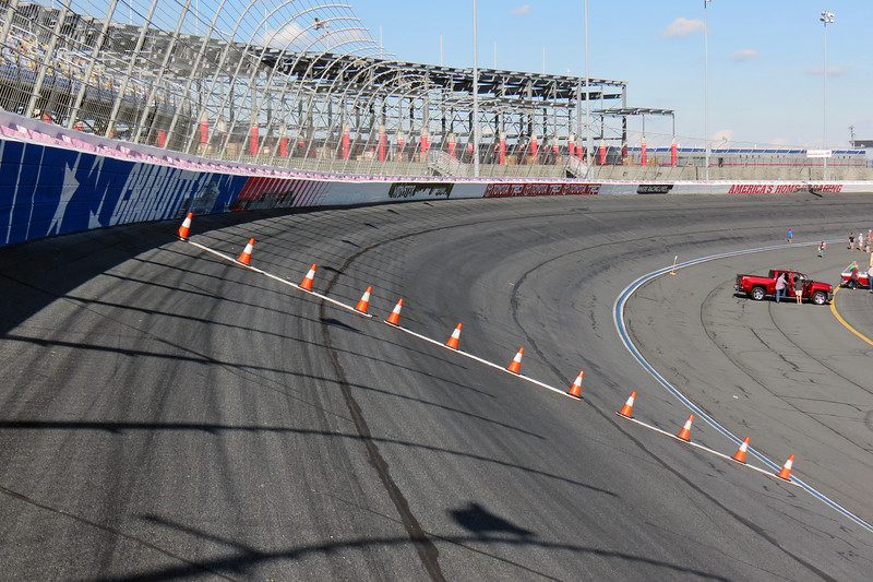 The turns at Charlotte Motor Speedway are banked at 24 degrees.  While this may not sound like much, it definitely is when you try to walk to the top of the track.