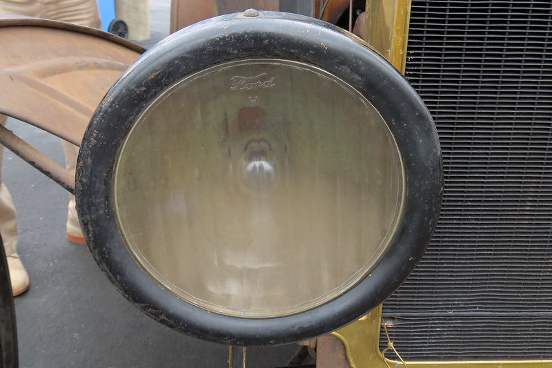 Early Model Ts used acetylene headlamps fueled by an acetylene generator mounted on the right running board.  The switch to electric headlamps occurred sometime around 1915.