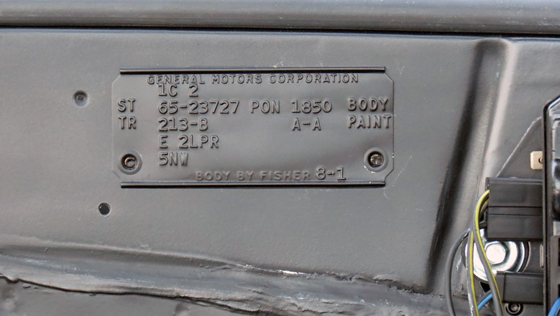 """The car's cowl tag.  Starting at the top .  .  .<br /> 1C = build date:  Third week of January 1965.  I'm not sure what the """"2"""" stands for.  The use of additional characters on the tag varied between assembly plants, the meanings of which have been lost to time.<br /> ST 65-23727 = style code:  65 = 1965, 2 = Pontiac, 37 = LeMans, 27 = 2-door sport coupe.<br /> PON = assembly plant:  Pontiac, Michigan.<br /> 1850 BODY = Fisher Body sequence number.<br /> TR 213-B = interior trim:  Black bucket seats.<br /> A-A PAINT = exterior paint codes:  Starlight Black upper and lower.<br /> E = Group 1 accessories:  E = Tinted glass, all windows.<br /> 2LPR = Group 2 accessories:  L = 4-speed floor shift transmission, P = radio, R = rear seat speaker.<br /> 5NW = Group 5 accessories:  N = GTO option package, (identifies the car as a legit GTO), W = retractable seat belts.<br /> 8-1 = More of those """"additional characters"""" mentioned above for which no information exists."""
