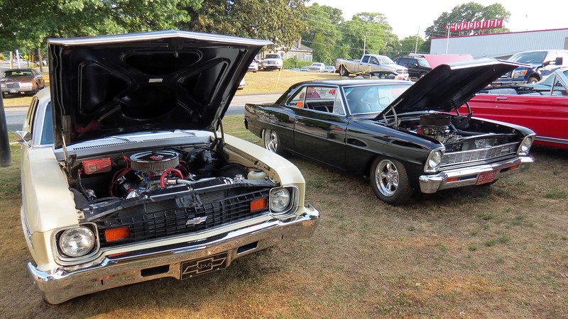 A pair of modified Chevrolet Novas.  The left car is a 1974 model and the right car is a 1966 model.