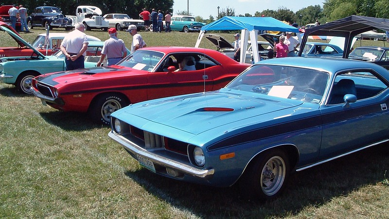 A pair of early '70s Mopars.  The red car is a 1972-74 Dodge Challenger, and the blue car is a 1972-74 Plymouth Barracuda.