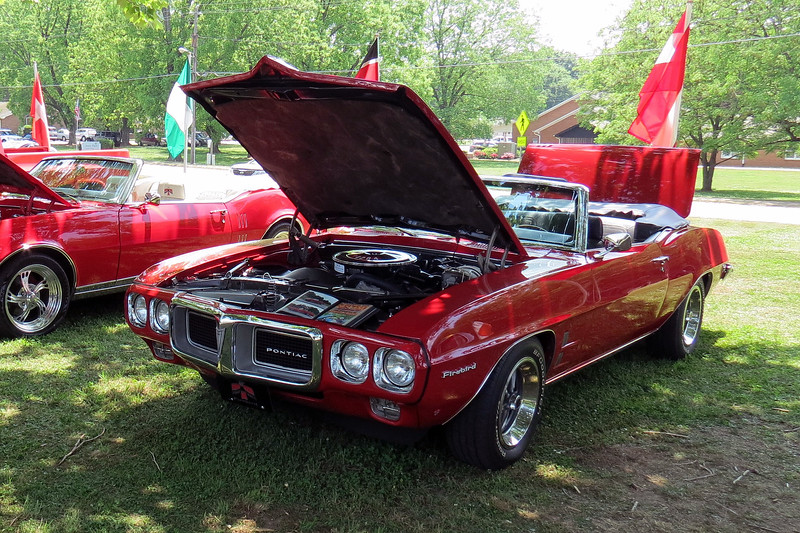 """The car on the right is a 1969 Pontiac Firebird convertible, one of 11,649 produced that year.  Keen eyes will spot the """"428-4"""" decal on the air cleaner which would seem to indicate the presence of the mighty 428 CID V8 under the hood.  Pontiac never put the 428 in a Firebird at the factory.  The swap was made during the car's comprehensive restoration, (which was fully documented via the book of photos displayed with the car)."""