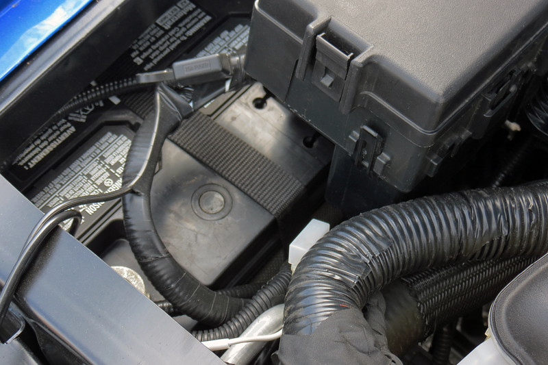The battery has been placed in a rather tight spot.  It's located in the right front corner of the engine bay partially under the right front fender.  But it's also under the fuse/relay box and almost directly against the upper radiator hose, a/c line, and engine wiring harness.