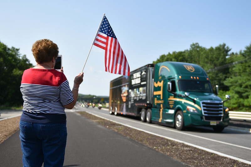 "June Gawson of Ashburnham watches as the ""Wall That Heals"" drives through Sterling and makes it's way  to Crocker's Park in Fitchburg on Wednesday where it will remain for the rest of the week.  SENTINEL & ENTERPRISE JEFF PORTER"