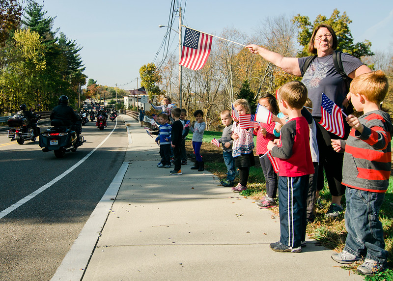 """Spectators gather in front of Johnny Ro Veteran's Memorial Park on Mechanic St. in Leominster as they await """"The Wall That Heals."""" The 250-foot replica of the Vietnam Wall traveled through the city on Wednesday morning and will be stationed at Carter Park through Sunday. SENTINEL & ENTERPRISE / Ashley Green"""