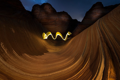 The Wave in a time lapse photo with a person running and waving a lighted wand