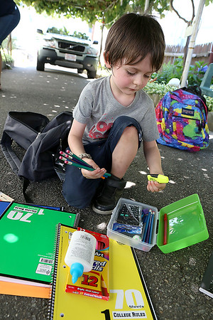 The Wish Project is having its yearly drive to collect backpacks for kids who need them for the school year. Timmy Martell, 4, looks through his backpack after receiving it. SUN/JOHN LOVE