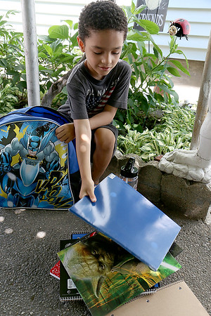 The Wish Project is having its yearly drive to collect backpacks for kids who need them for the school year. Jay Ortiz, 5, looks through his backpack after receiving it. SUN/JOHN LOVE