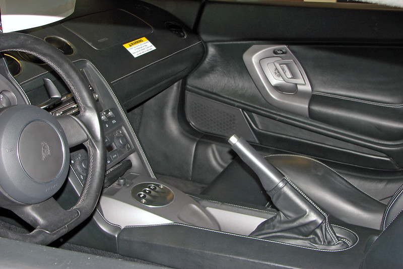 Normally, this car would be fitted with a traditional 3-pedal manual transmission.  But the lack of any kind of gear shift lever indicates that this car has Lamborghini's E-Gear 6-speed automated manual transmission.