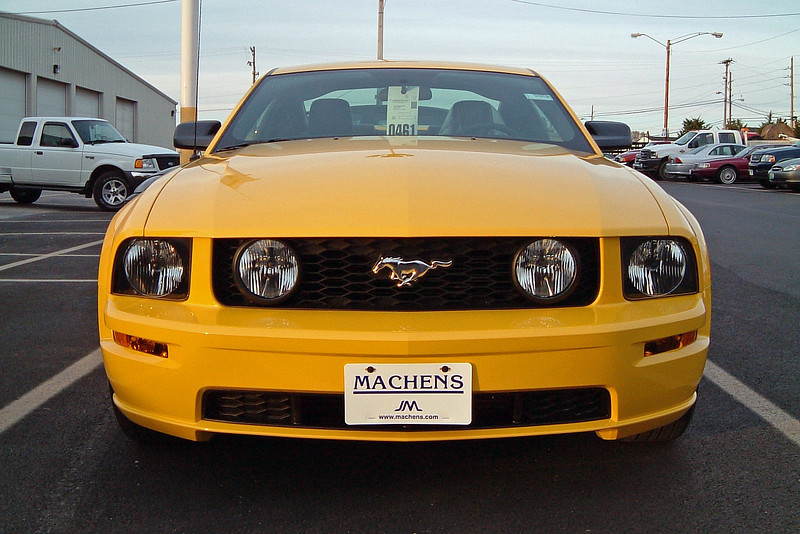 The yellow car is a V8 powered Mustang GT.